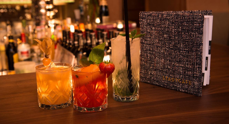Drei Cocktails und Karte auf der Bar